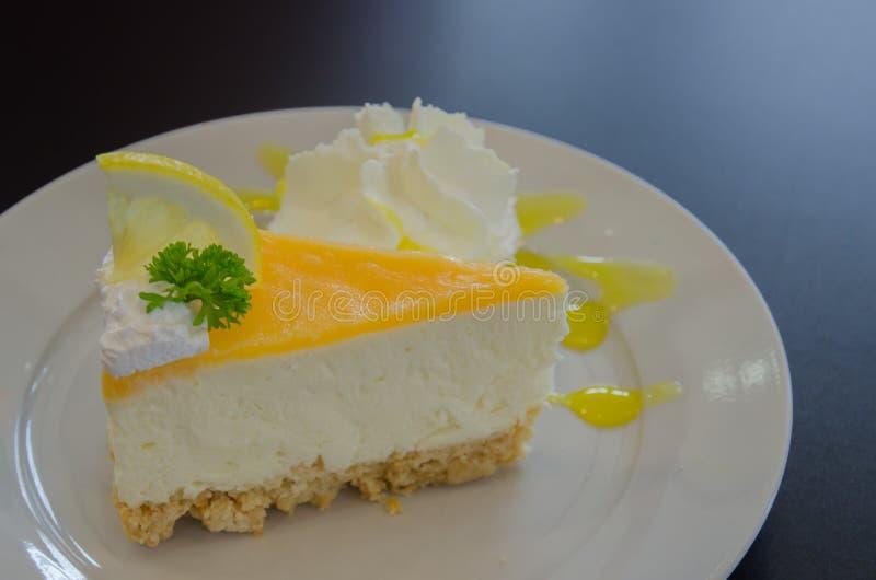 pedazo de pastel de queso del limón en la placa blanca fotos de archivo