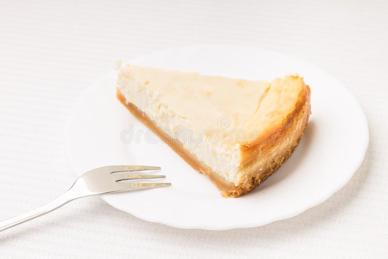 Pedazo de pastel de queso en el platillo blanco imagen de archivo