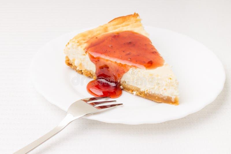 Pedazo de pastel de queso en el platillo blanco foto de archivo