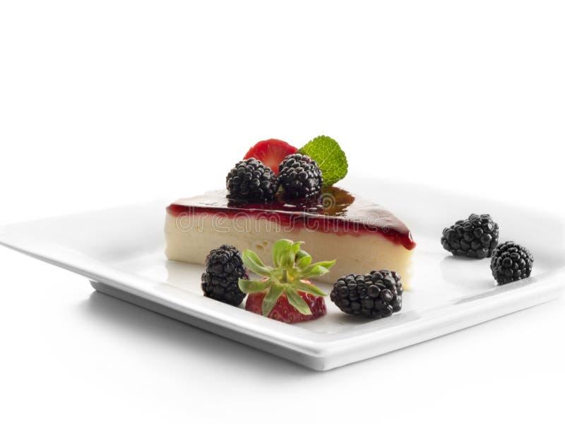 Pedazo de pastel de queso adornado con las fresas y las frambuesas negras fotos de archivo libres de regalías