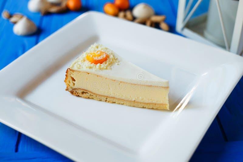 Pedazo de pastel de queso cortado en el servicio ajustado blanco del primer de la placa fotografía de archivo