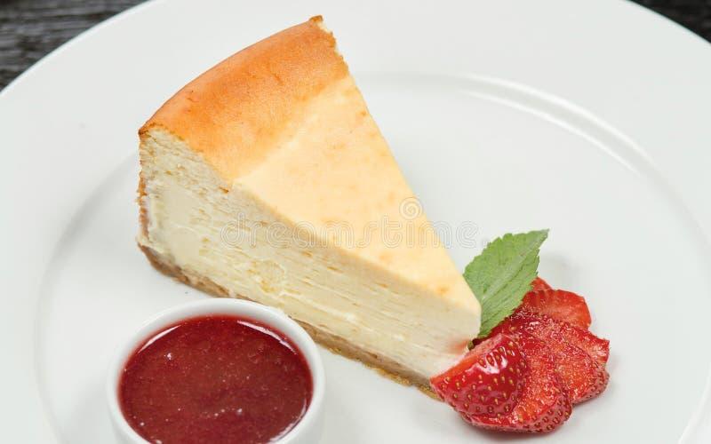 Pedazo de pastel de queso en una placa blanca, adornado con las rebanadas y piracotta frescos de la fresa con la mermelada de fre imagenes de archivo