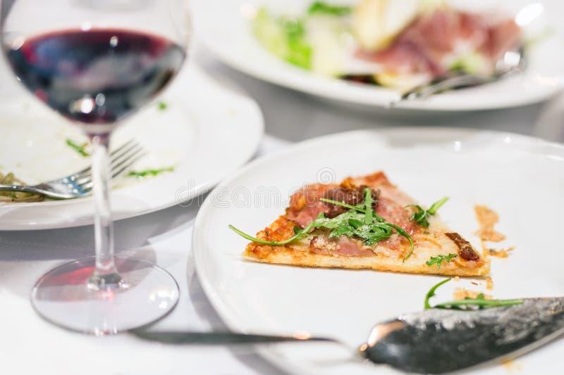 Pedazo de pizza pasado en la placa blanca Pedazos y leftobers de la comida en la tabla después del problema del banquete de la ob imagen de archivo libre de regalías
