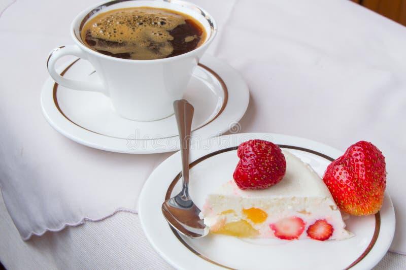 Pedazo de postre de la fresa en la placa y el café blancos de la taza foto de archivo