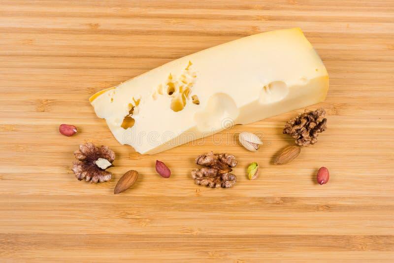 Pedazo de queso del maasdam y de diversas nueces en superficie de madera foto de archivo libre de regalías