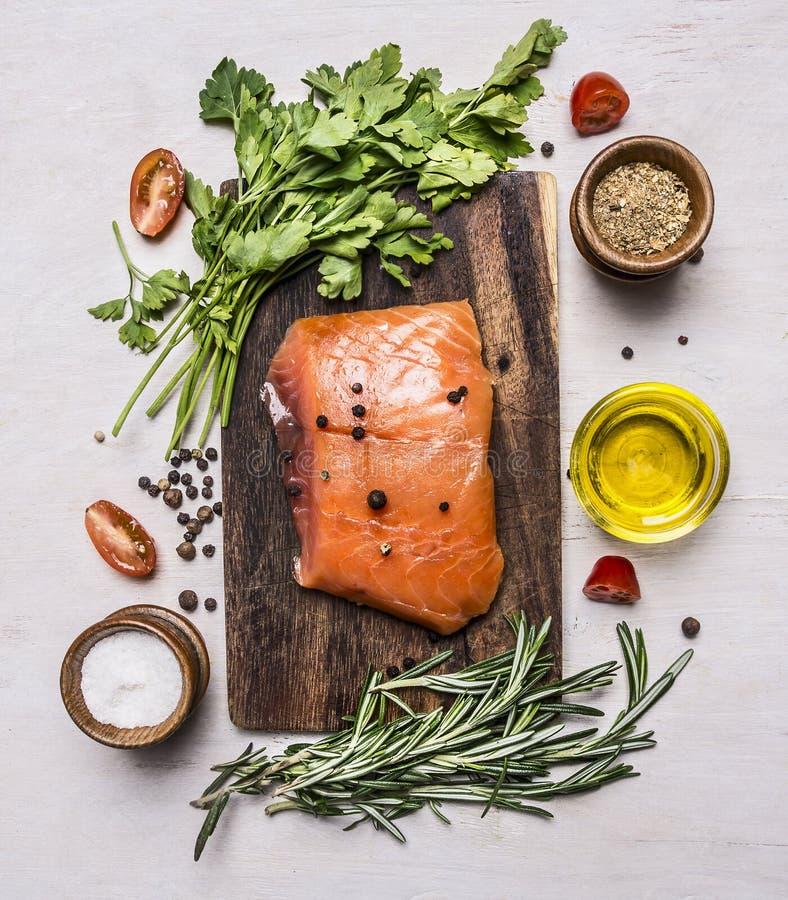 Pedazo de salmón ahumado en una tabla de cortar con la opinión superior del fondo rústico de madera de las hierbas y de las espec imagenes de archivo