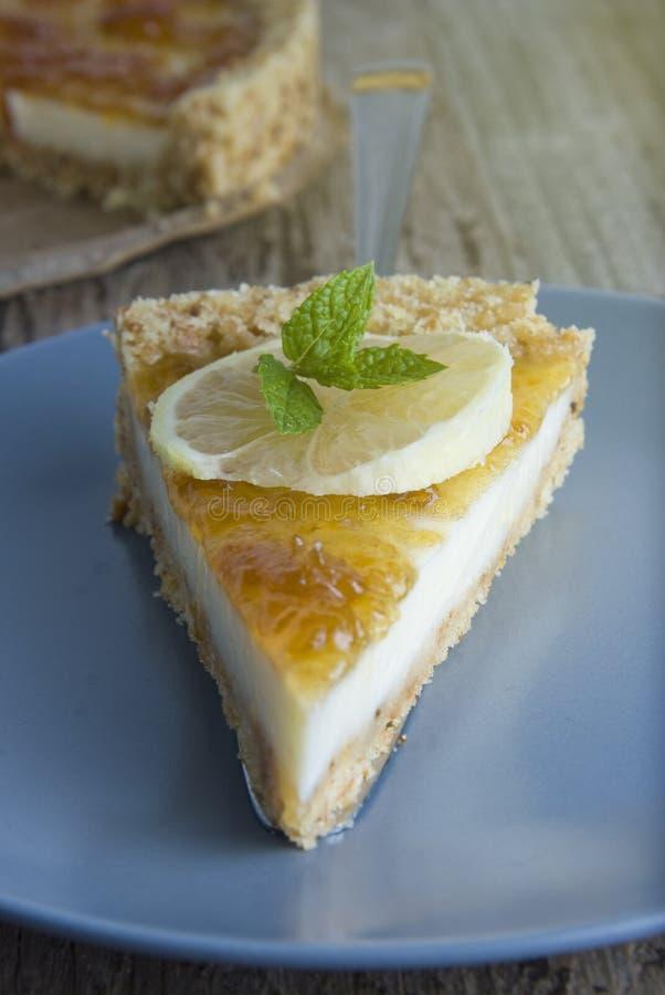 Pedazo de tarta hecha en casa del limón o de la fruta cítrica La torta dulce con el limón y la fruta cítrica atascan en la placa  fotos de archivo