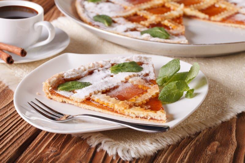 Pedazo de tarta italiana con el atasco y el café del albaricoque fotografía de archivo libre de regalías