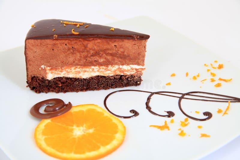 Pedazo de torta de chocolate con la decoraci?n en la placa blanca foto de archivo libre de regalías
