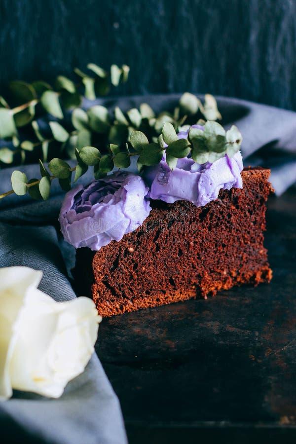 Pedazo de torta de chocolate del cumplea?os con las rosas poner crema p?rpuras imagen de archivo libre de regalías