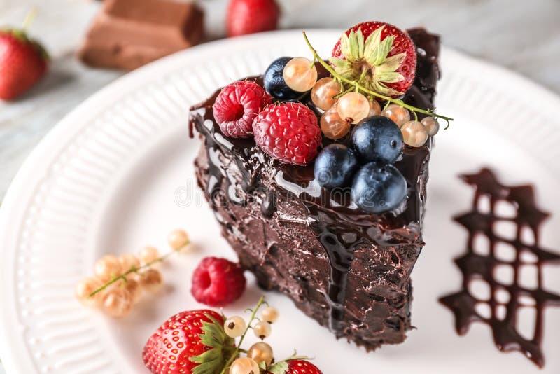 Pedazo de torta de chocolate deliciosa con las bayas en la placa, primer imagenes de archivo