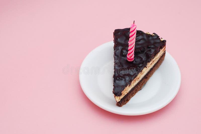 Pedazo de torta de cumpleaños del chocolate con la vela en la placa blanca sobre el fondo rosado para el texto horizontal Partido imagenes de archivo