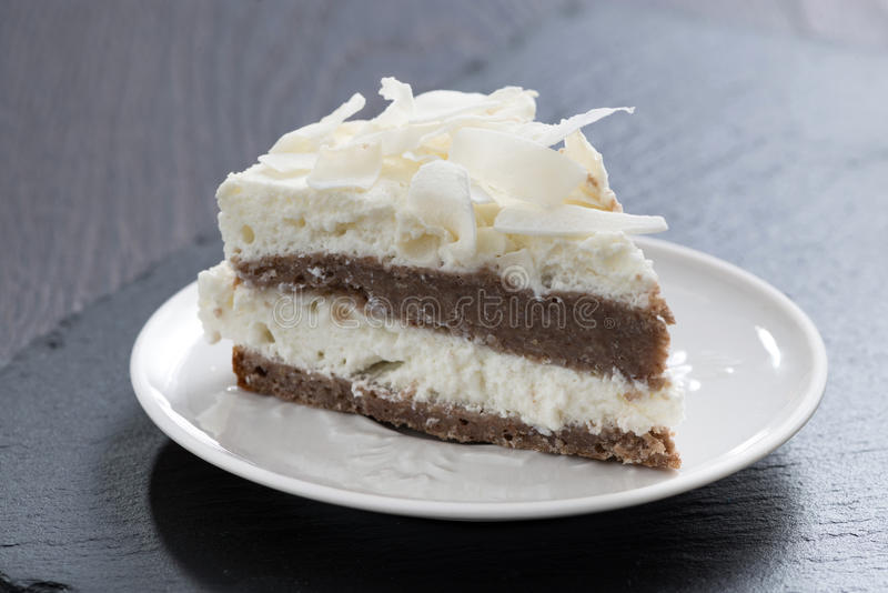 Pedazo de torta de chocolate con crema del coco imagenes de archivo