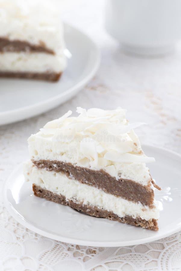 Pedazo de torta de chocolate deliciosa con crema del coco, vertical imágenes de archivo libres de regalías