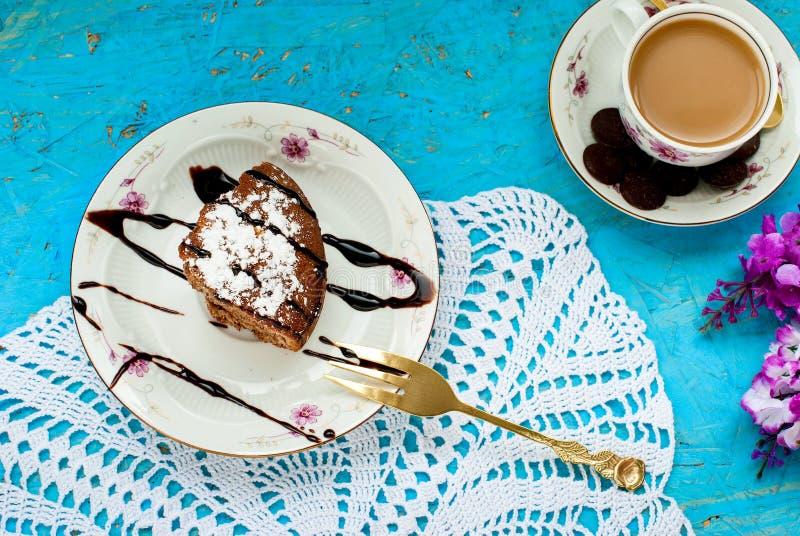 Pedazo de torta de chocolate y de una taza de café con leche fotos de archivo libres de regalías