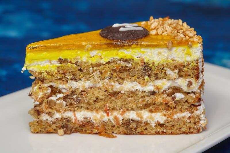 Pedazo de torta de zanahoria con la formación de hielo y la nuez en la placa foto de archivo
