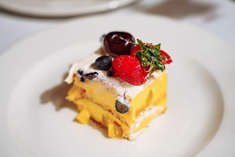 Pedazo de torta deliciosa con las bayas en una placa blanca Profundidad del campo baja imágenes de archivo libres de regalías
