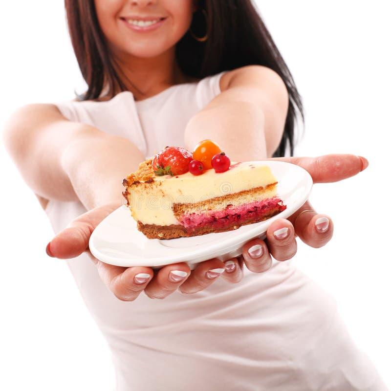 Pedazo de torta en manos de la mujer fotografía de archivo libre de regalías