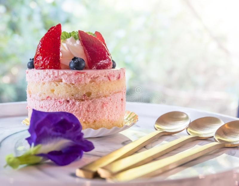 Pedazo de torta hecha en casa acodada multi y de bayas frescas adornadas con el guisante de mariposa fotos de archivo libres de regalías