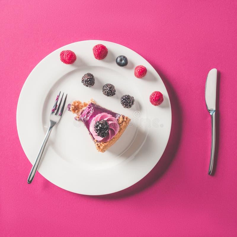 Pedazo de torta mordido con las bayas en la placa en superficie rosada imagen de archivo