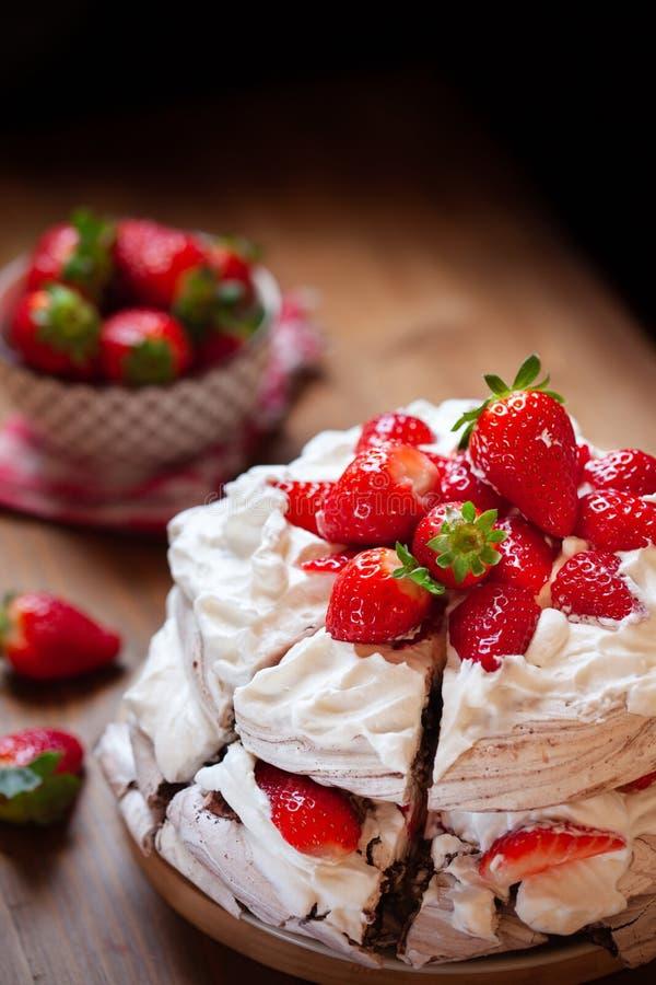 Pedazo de torta Pavlova del merengue del chocolate con crema azotada y la fresa fresca fotos de archivo libres de regalías