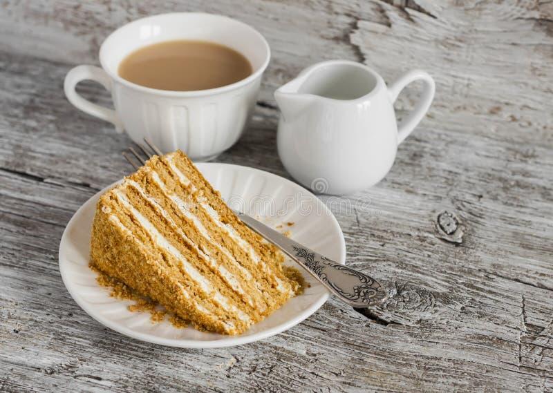 Pedazo de torta y de té de miel con leche foto de archivo