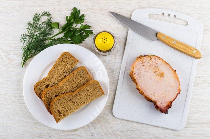 Pedazo del carbonade, cuchillo en la tabla de cortar, pan, verdes, peppe imágenes de archivo libres de regalías