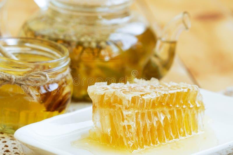 Pedazo del peine de la miel Rebanada de la miel con infusión de hierbas y el tarro de miel en la tabla de madera pieza de panal c imagenes de archivo