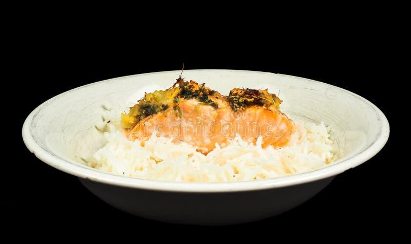 Pedazo delicioso de salmones en una cama del arroz granuloso largo foto de archivo