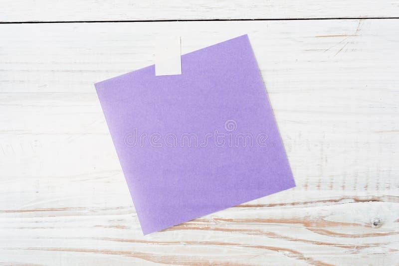 Pedazo en blanco de papel de nota púrpura imagenes de archivo