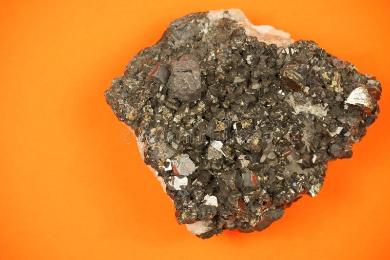 Pedazo entero de formación del bloque del mineral del grafito con textura irregular, tiro en fondo de papel anaranjado fotografía de archivo libre de regalías