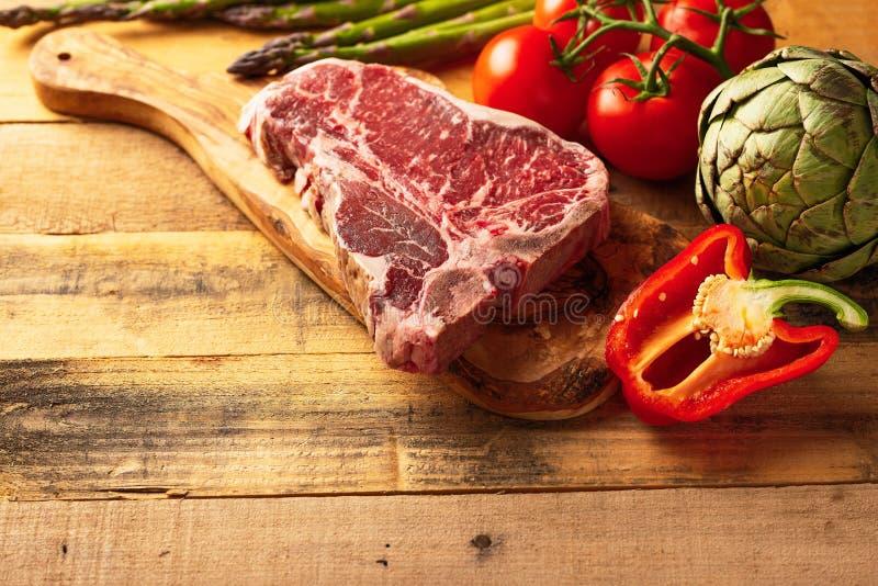 Pedazo fresco jugoso de filete de carne de vaca veteado con las verduras para asar a la parrilla Fondo culinario, libro de la rec fotografía de archivo libre de regalías
