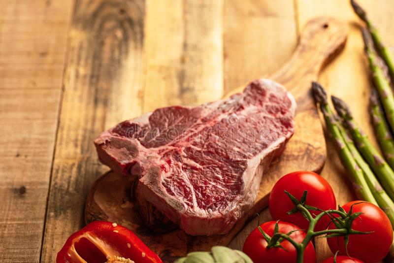 Pedazo fresco jugoso de filete de carne de vaca veteado con las verduras para asar a la parrilla Fondo culinario, libro de la rec fotografía de archivo