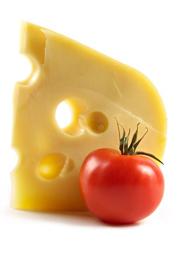 Pedazo grande de queso y de tomates fragantes de la élite imagen de archivo