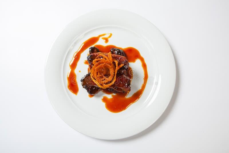 Pedazo jugoso de cordero debajo de la salsa dulce roja y cubierto con la cebolla frita en la placa blanca redonda grande en el fo imágenes de archivo libres de regalías