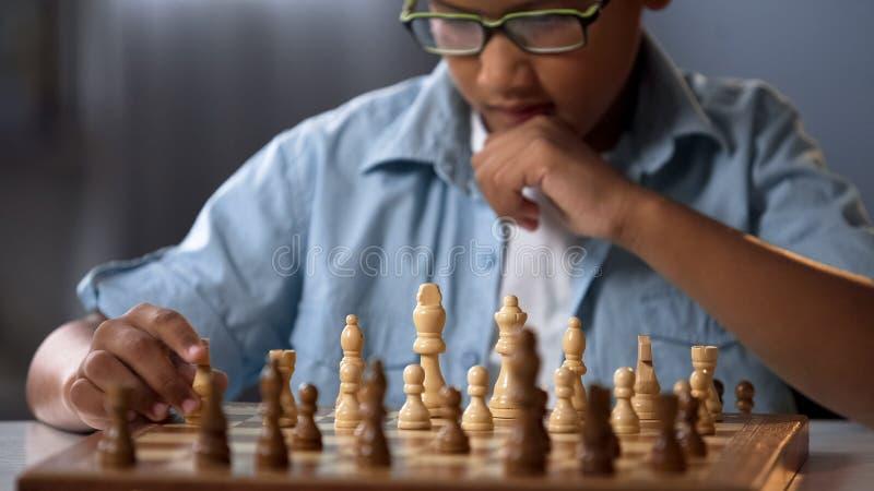 Pedazo móvil del caballero del niño africano durante el torneo del ajedrez, análisis de la estrategia del juego imagenes de archivo