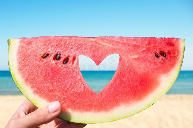 Pedazo maduro de sandía con el agujero de la forma del corazón en manos femeninas en el fondo de la playa en un día de verano cal foto de archivo