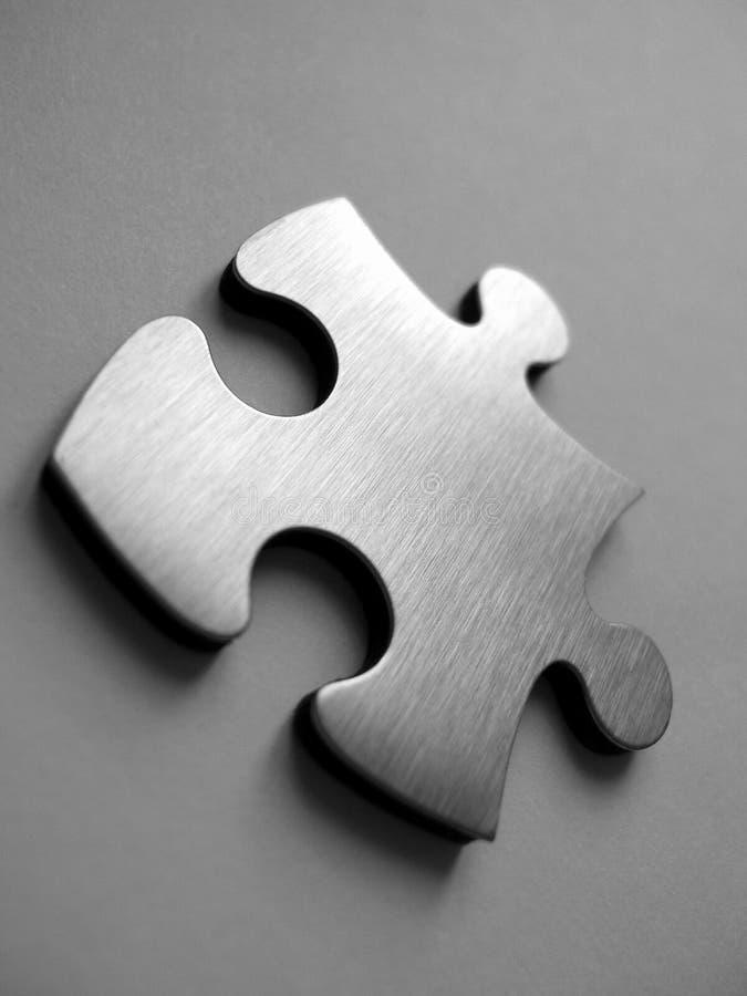 Pedazo metálico de los rompecabezas foto de archivo libre de regalías
