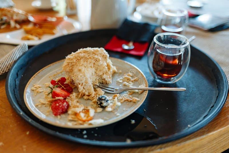 Pedazo mordido de torta poner crema azotada, de una taza de té y de una cuchara en una bandeja redonda negra en una tabla en un c fotografía de archivo libre de regalías