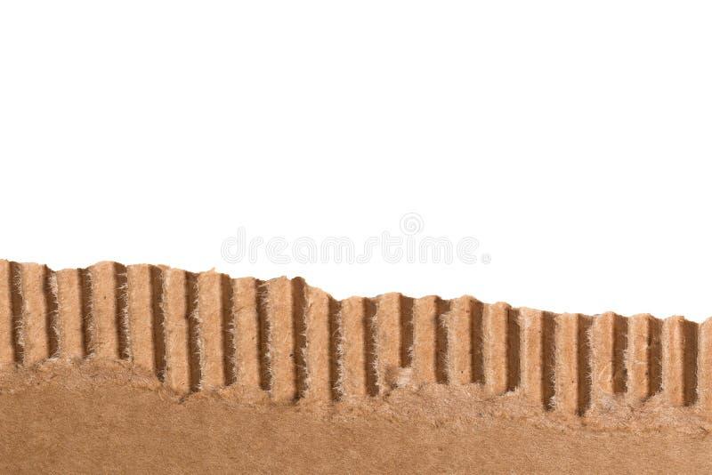 Pedazo rasgado de la cartulina acanalada de Brown en el fondo blanco foto de archivo