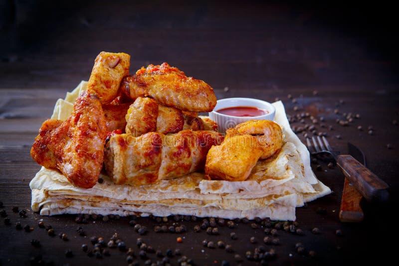 Pedazos clasificados de pollo frito Platos de la parrilla para el menú del restaurante Fondo de madera imágenes de archivo libres de regalías