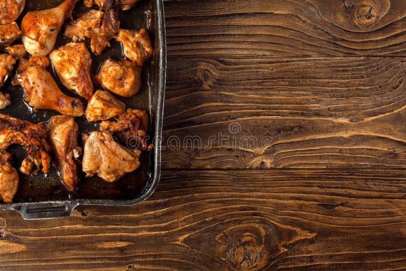 Pedazos cocidos del pollo en el molde para el horno foto de archivo