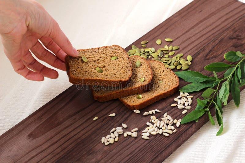 Pedazos cortados de mentira del pan de centeno en una tabla de cortar de madera la mano pone y toma un pedazo de pan foto de archivo