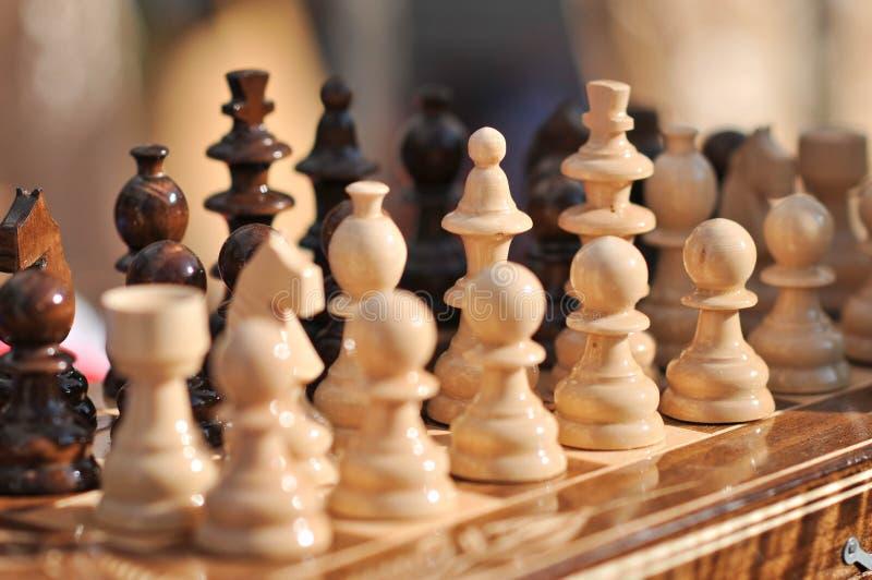 Pedazos de ajedrez blancos y negros en un tablero de ajedrez, primer El conjunto de ajedrez calcula en la tarjeta que juega imagenes de archivo