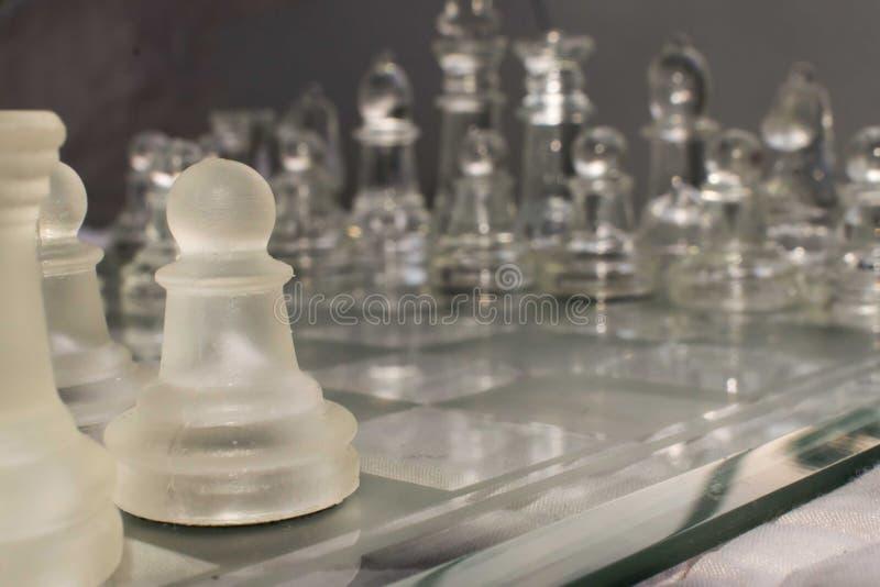 Pedazos de ajedrez de cristal dispuestos en un tablero de ajedrez de cristal fotografía de archivo libre de regalías