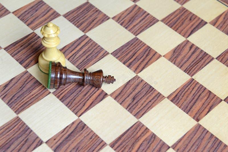 Pedazos de ajedrez de madera en el tablero de ajedrez imagen de archivo libre de regalías