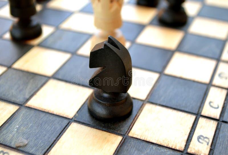 Pedazos de ajedrez en una tarjeta de ajedrez imagenes de archivo