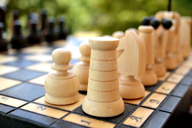 Pedazos de ajedrez en una tarjeta de ajedrez foto de archivo