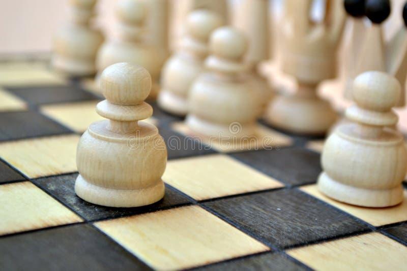 Pedazos de ajedrez en una tarjeta de ajedrez fotografía de archivo