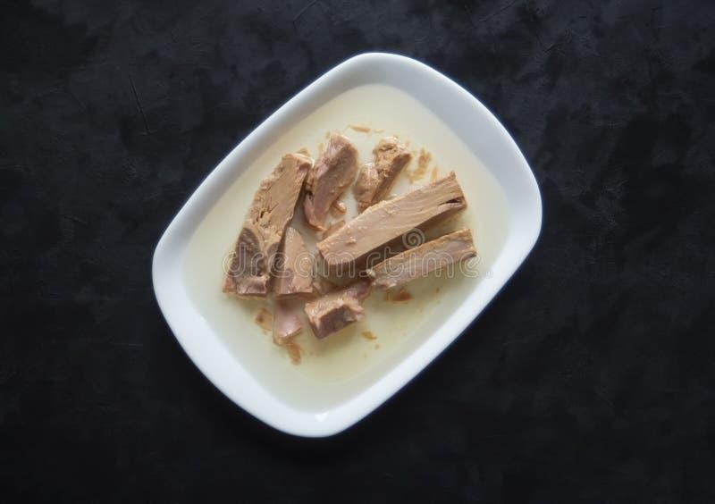 Pedazos de atún en una placa blanca Pescados conservados imagen de archivo
